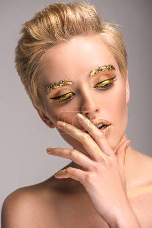 Foto de Mujer atractiva con brillo dorado en la cara tocando labios aislados en gris - Imagen libre de derechos
