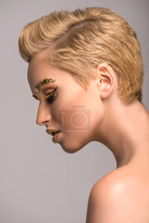 side view of attractive woman with golden glitter on face isolated on grey
