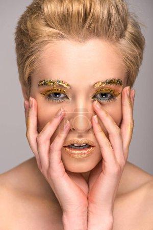 Photo pour Belle fille avec golden maquillage étincelant toucher visage isolé sur fond gris - image libre de droit