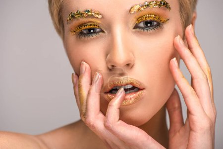 attractive woman with golden glittering makeup touching face isolated on grey
