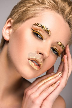 sensual attractive woman with golden glitter on face looking at camera isolated on grey