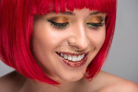 Foto de Sonriente mujer atractiva con el pelo rojo y brillo en la cara aislado en gris - Imagen libre de derechos