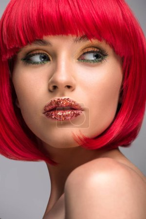 Photo for Portrait of beautiful woman with red hair and glitter on face looking away isolated on grey - Royalty Free Image