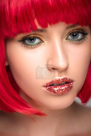 headshot of attractive woman with red hair and sparkling makeup looking at camera
