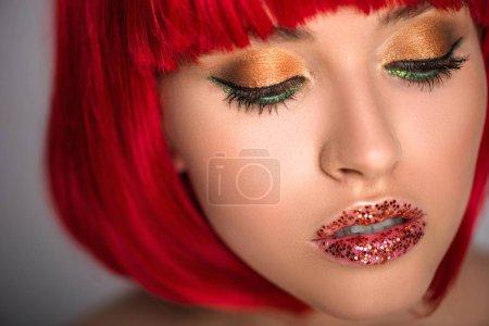 Photo pour Jolie femme avec les cheveux rouges et maquillage étincelant, regardant vers le bas - image libre de droit