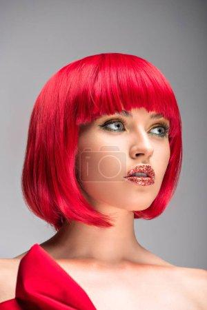 Foto de Vista de ángulo bajo de mujer atractiva con el pelo rojo y brillo en la cara mirando a aislado en gris - Imagen libre de derechos