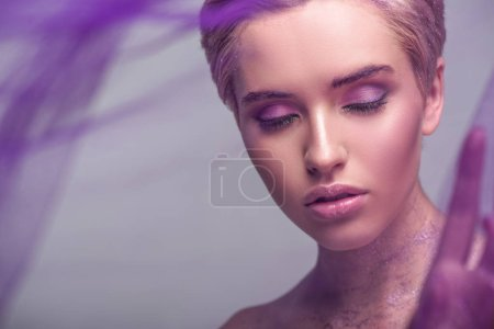 attractive woman with violet glitter on neck standing with closed eyes isolated on grey