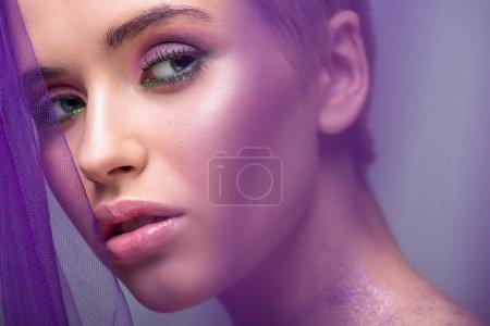 Foto de Hermosa mujer con maquillaje violeta mirando lejos aislada en gris - Imagen libre de derechos