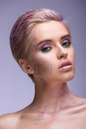 Foto de Mujer atractiva con brillo violeta en el cuello y pelo corto mirando a cámara aislada en violeta - Imagen libre de derechos