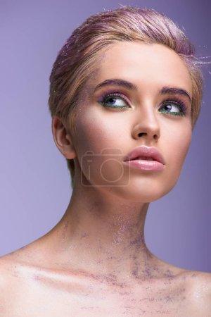 Foto de Mujer atractiva con brillo violeta en el cuello y pelo corto buscando aislados en violeta - Imagen libre de derechos