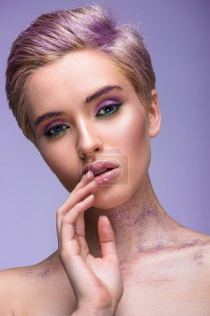 attractive woman with violet glitter on neck and short hair touching lips isolated on violet