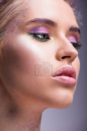 Photo pour Tête de femme attirante avec des paillettes violettes sur cou vous cherchez loin isolé sur violet - image libre de droit