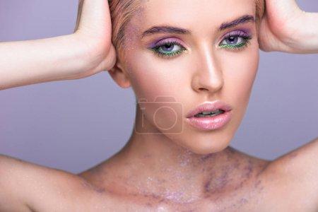 Foto de Hermosa mujer con brillo violeta cuello tocar cabeza aislada en violeta - Imagen libre de derechos