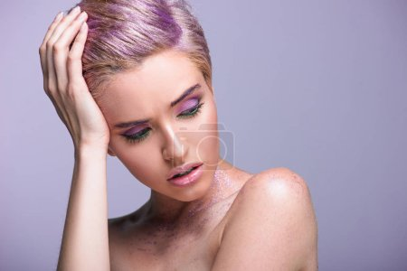 beautiful woman with violet glitter on neck and short hair looking down isolated on violet