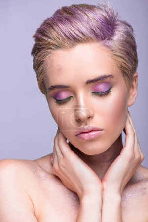 attractive woman with violet glitter on neck and short hair touching neck with closed eyes isolated on violet