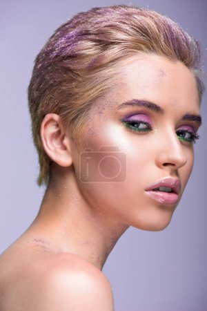 attractive woman with violet glitter on neck and short hair looking at camera isolated on violet