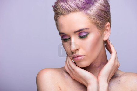attractive woman with violet glitter on neck and short hair looking down isolated on violet