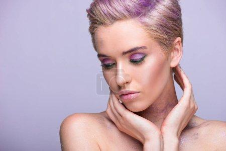 Photo pour Jolie femme avec des paillettes violettes sur le cou et les cheveux courts, regardant vers le bas violet isolée sur - image libre de droit