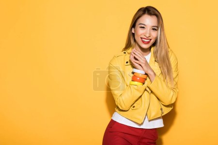 smiling young asian woman standing on yellow background
