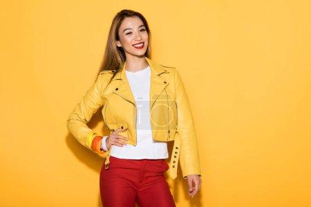stylish young asian woman on yellow background
