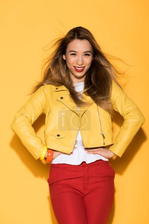 attractive young asian woman in leather jacket posing on yellow background