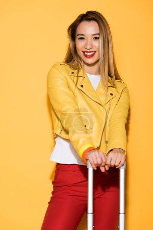 stylish female traveler with wheeled bag on yellow background