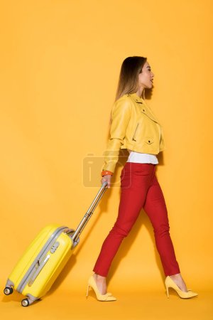 side view of stylish asian female traveler carrying wheeled bag on yellow background