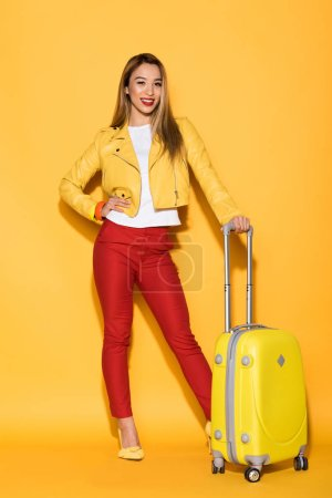smiling asian female traveler standing with wheeled bag on yellow background