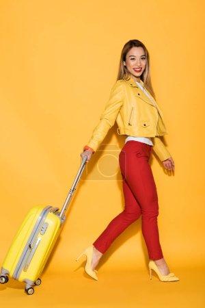 smiling female traveler carrying wheeled bag on yellow background