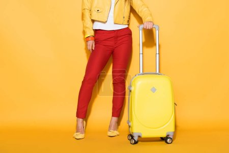 Photo pour Plan recadré de voyageuse élégante debout avec sac à roulettes sur fond jaune - image libre de droit