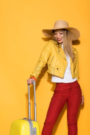 stylish asian female traveler in straw hat standing with wheeled bag on yellow background