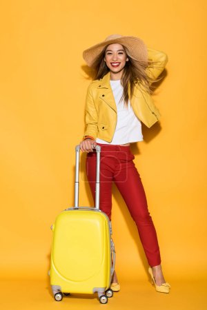 happy stylish female traveler in straw hat standing with wheeled bag on yellow background