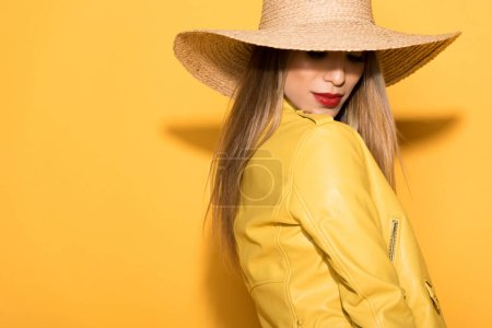 Photo for Attractive asian female model in straw hat posing on yellow background - Royalty Free Image