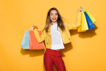 Photo for Smiling stylish asian woman with shopping bags on yellow background - Royalty Free Image