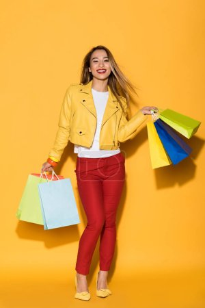 Photo for Happy asian female shopaholic with paper bags on yellow background - Royalty Free Image