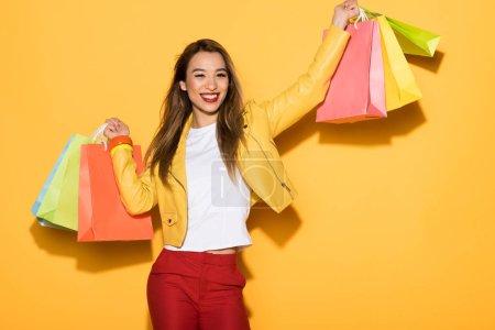 Photo pour Sourire asiatique femme avec des sacs à provisions sur fond jaune - image libre de droit