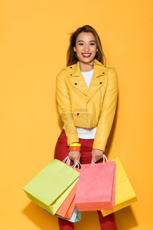 happy female shopaholic standing with paper bags on yellow background