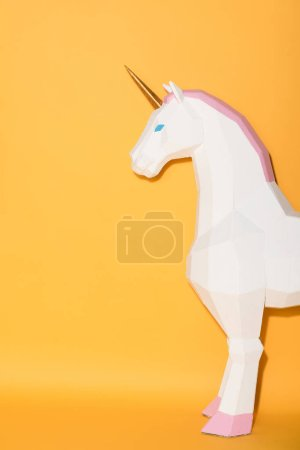 partial view of decorative unicorn standing on yellow background
