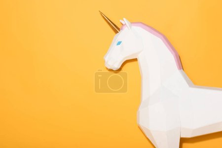 side view of decorative unicorn standing on yellow background