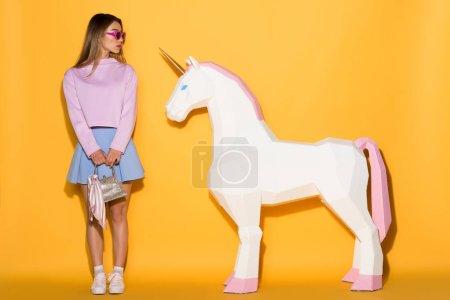 Foto de Joven modelo hembra asiático en gafas de sol con bolso y unicornio decorativo sobre fondo amarillo - Imagen libre de derechos