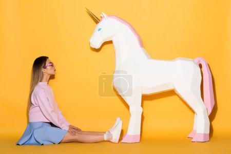 Foto de Vista lateral del modelo hembra asiático en gafas de sol sentado en el piso y unicornio decorativo sobre fondo amarillo - Imagen libre de derechos