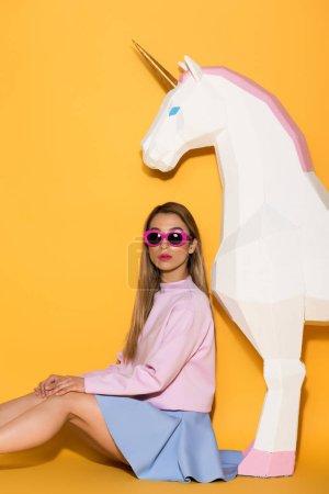 stylish asian female model in sunglasses and decorative unicorn on yellow background