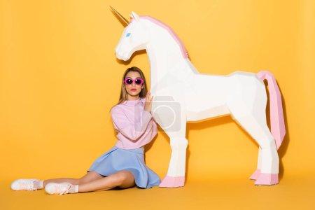 Foto de Modelo de mujer joven en gafas de sol sentado en el piso y abrazar unicornio decorativo sobre fondo amarillo - Imagen libre de derechos