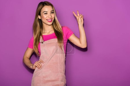 smiling asian female model doing peace gesture on purple background