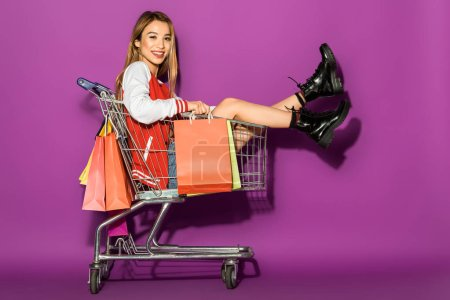 Photo for Beautiful asian woman with shopping bags sitting in shopping trolley and smiling at camera on violet - Royalty Free Image