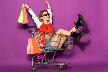 Photo for Beautiful happy young woman in sunglasses holding paper bags and sitting in shopping trolley on violet - Royalty Free Image