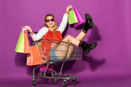 beautiful young woman in sunglasses holding shopping bags and sitting in shopping trolley on violet