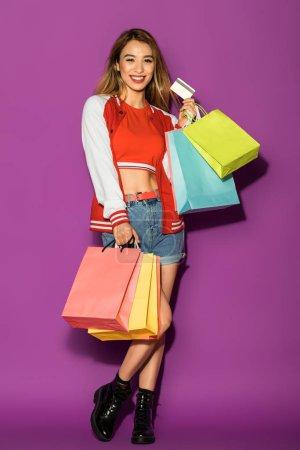 Photo pour Heureux asiatique fille avec shopping sacs tenant carte de crédit et sourire à caméra isolé sur violet - image libre de droit