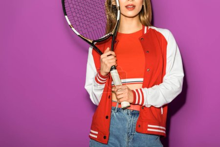 cropped shot of young woman holding tennis racquet isolated on violet