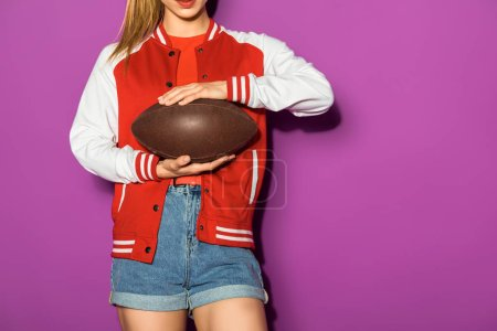cropped shot of sporty young woman holding rugby ball isolated on violet